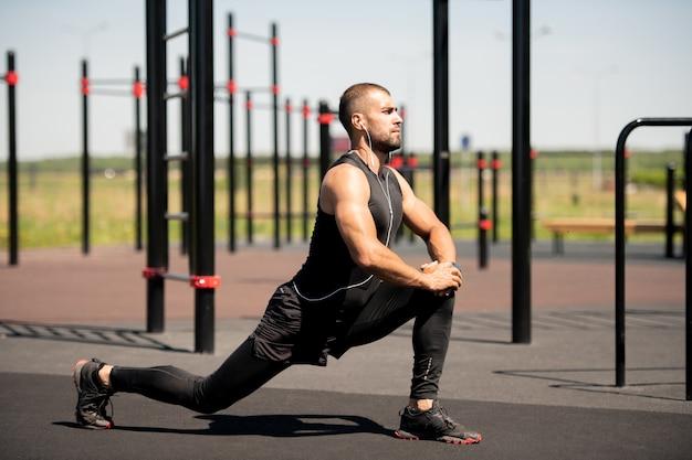 Sterke jonge atleet in activewear doet oefening voor het strekken van benen op buitensportterrein op uw gemak