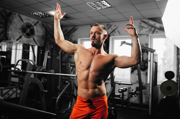 Sterke jonge bodybuilder ziet er goed uit, gespierde bodybuilder knappe mannen doen oefeningen in de sportschool