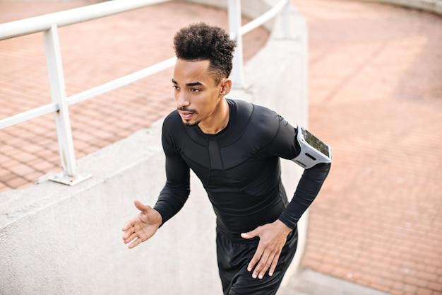 Sterke jonge brunet man in zwart t-shirt met lange mouwen en korte broek die naar boven rent
