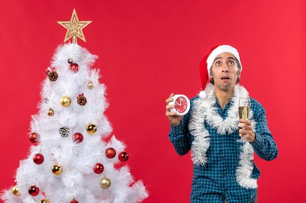 Sterke jonge kerel met de hoed van de kerstman en het opheffen van een glas wijn en het houden van klok die zich dichtbij kerstboom op rood bevindt