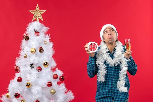 Sterke jonge kerel met de hoed van de kerstman en met een glas wijn en een klok die zich dichtbij kerstboom op rood bevinden