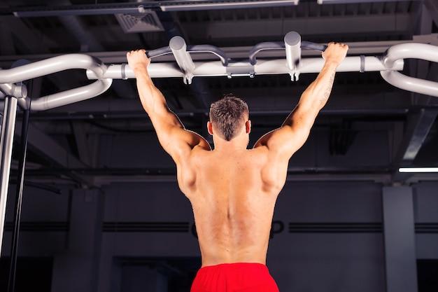 Sterke jonge man doet pull-up oefening op horizontale balk in de sportschool. sport, fitness, gymnastiektraining.