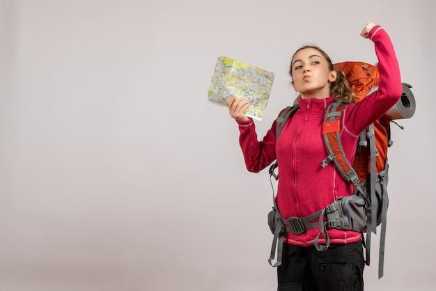 Sterke jonge reiziger met grote rugzak die kaart omhoog houdt
