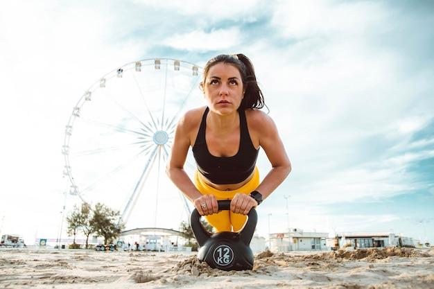 Sterke jonge vrouw die push-ups doet op het strand