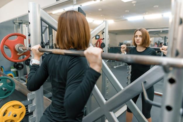 Sterke jonge vrouw die zwaargewicht training in gymnastiek doet