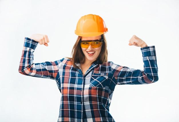 Sterke jonge vrouw in oranje helm en veiligheidsbril, plaidoverhemd die spieren tonen die op wit worden geïsoleerd