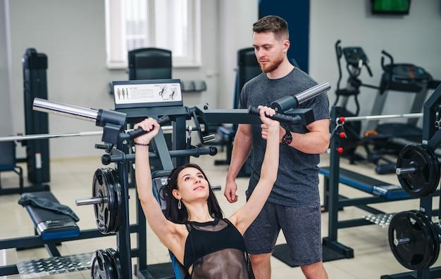 Sterke jonge vrouw met mooi atletisch lichaam die oefeningen met barbell doet.
