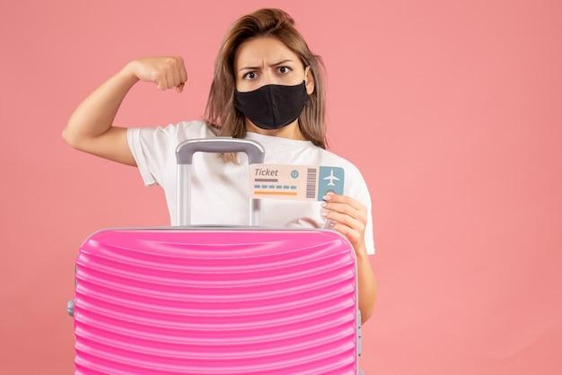 Sterke jonge vrouw met zwart masker met kaartje achter roze koffer pink