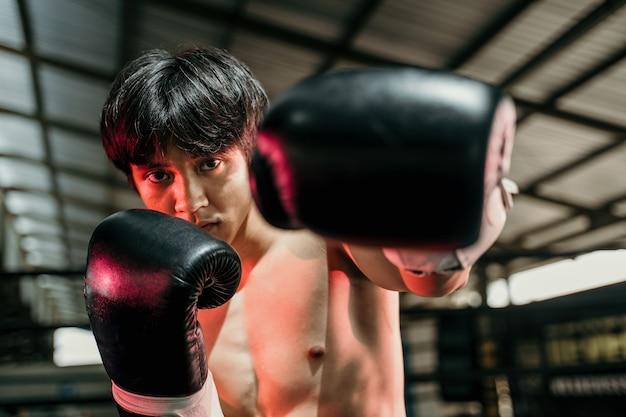 Sterke jongeman staan met bokshandschoenen met vuisten in de arena
