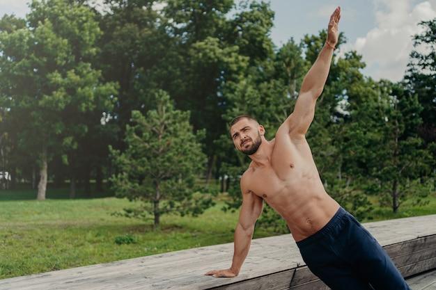 Sterke jongeman staat in zijplank op één arm, vindt balans, poseert in het park in de buurt van bomen, beoefent yoga buiten, leidt een actieve, gezonde levensstijl, heeft een krachtig lichaam.