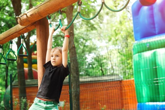 Sterke kleine jongen buiten opleiding. kinderen sporten buitenshuis. leuke jongen spelen op monkey bars.