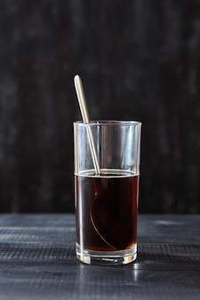 Sterke koffie in een transparant glas met een lepel op een donkere houten tafel