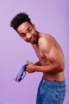 Sterke lachende man die zich voordeed op pastel paarse muur. binnenfoto van geïnteresseerde afrikaanse man zonder t-shirt.