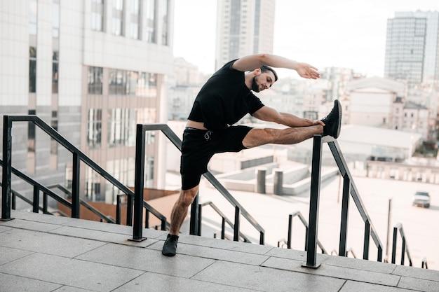 Sterke man aan het opwarmen. ochtend activiteit. man die zijn armen uitstrekt en wegkijkt. ochtendtraining met leuning. zwarte sportkleding. fit man doet kantelen van het lichaam naar de zijkant buiten.
