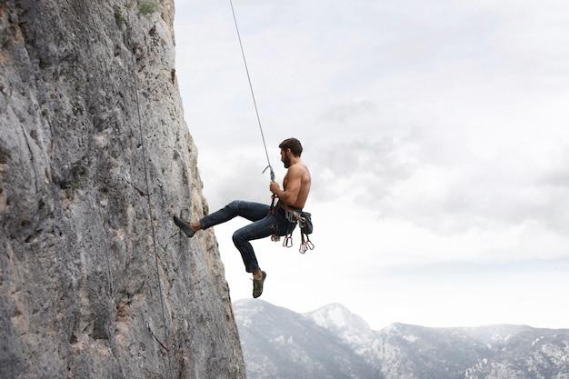 Sterke man die op een berg klimt met veiligheidsuitrusting