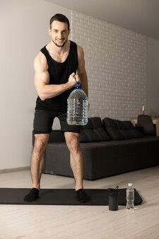 Sterke man die thuis oefeningen voor het opvoeden van kalveren met een grote fles water oefent. gezonde geest in sterk lichaamsconcept. gezellige woonkamer op de achtergrond. man in zwarte sportkleding die ochtendtraining doet.