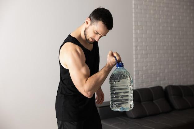 Sterke man doet thuis kuitoefeningen met een grote fles water in zijn ruime en lichte appartement met minimalistisch interieur. man in zwarte sportkleding die ochtendtraining doet.