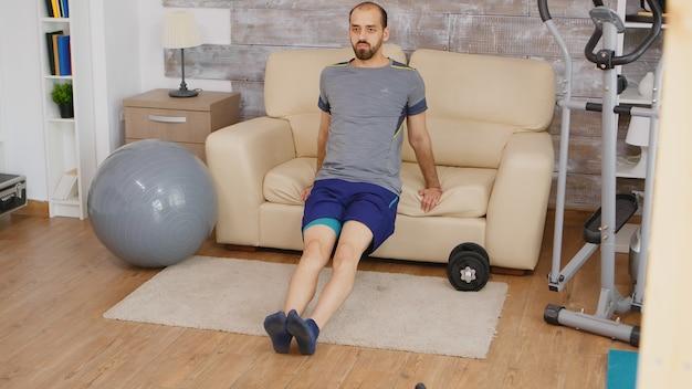 Sterke man doet triceps-training met behulp van de bank in de woonkamer met sportkleding.