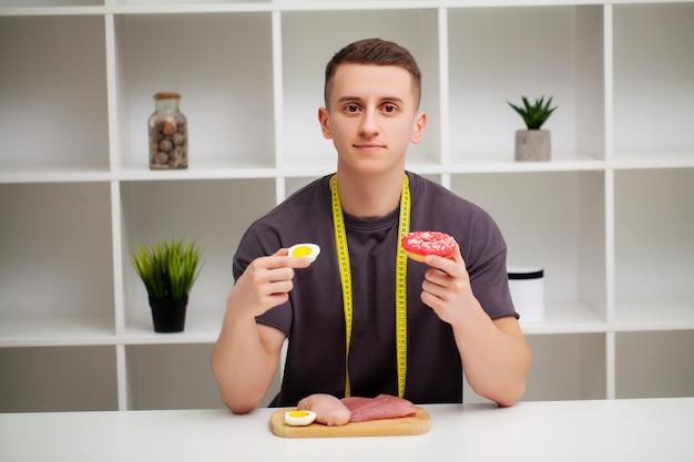 Sterke man eet een eiwitrijke maaltijd van vlees en donut.