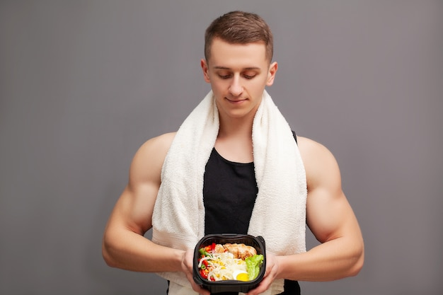Sterke man eet een eiwitrijke maaltijd van vlees en fruit