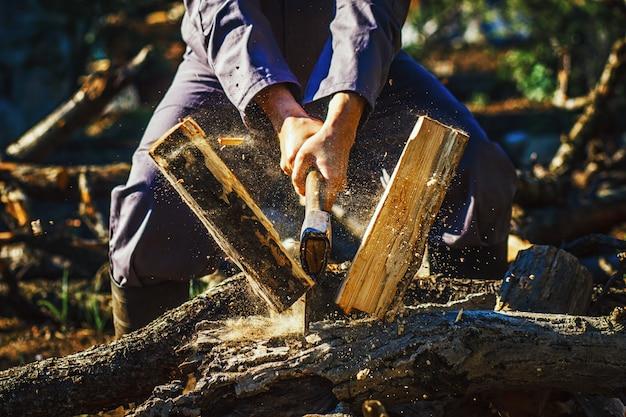 Sterke man houthakker met een bijl in zijn hand. kettingzaag close-up.