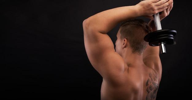 Sterke man maakt oefeningen op triceps. gespierd lichaam met vrije ruimte voor fitnessartikelen. close-up shot training handen. twee-armige triceps-extensie