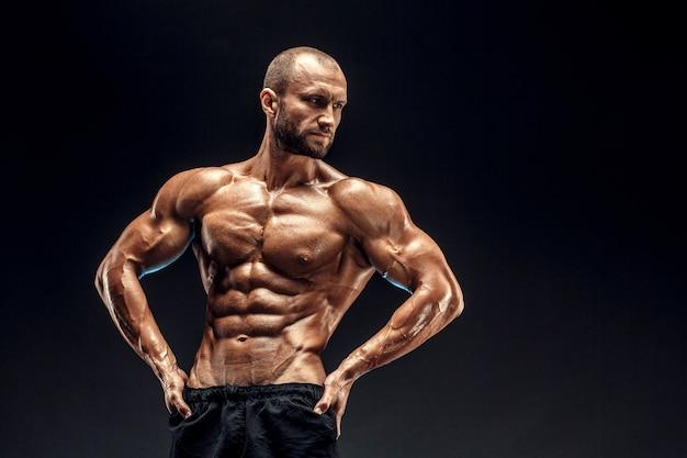 Sterke man met perfecte buikspieren, schouders, biceps, triceps en borst. bodybuilder topless buigen zijn spieren over zwarte muur.