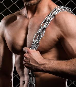 Sterke man op hek met kettingen