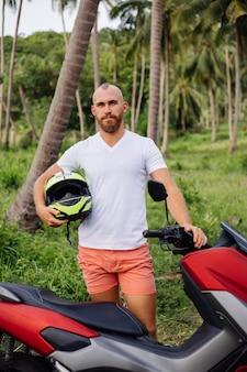 Sterke man op tropische jungle veld met rode motor