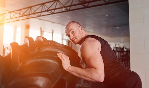 Sterke man pakt een groot zwaar rubberen wiel. functionele training