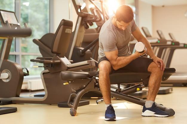 Sterke man pompen spieren in de sportschool