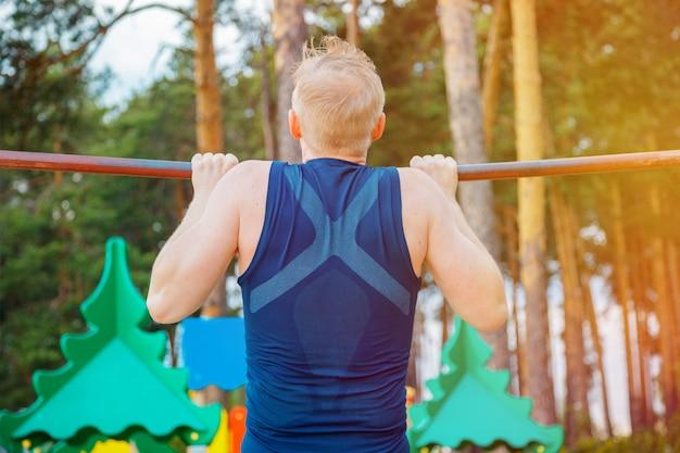 Sterke man pull-ups op een balk buiten doen