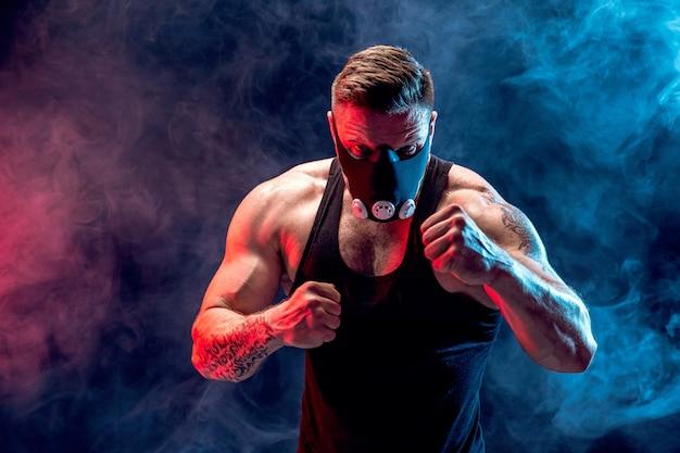 Sterke mannelijke atleet in een zwart trainingsmasker op een zwarte muur