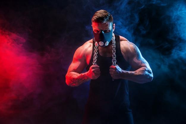 Sterke mannelijke atleet in een zwarte opleiding masker op een zwarte muur