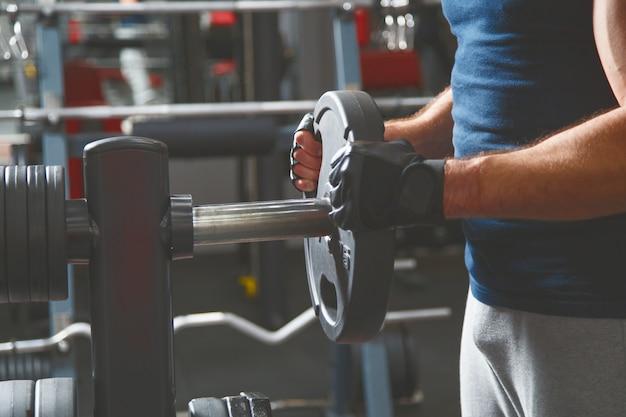 Sterke mannelijke bodybuilder met barbellpannekoeken