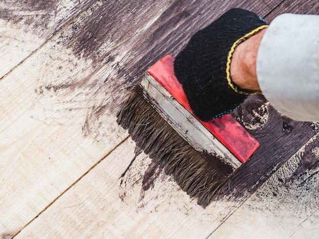 Sterke mannelijke handen die houten raad schilderen. detailopname