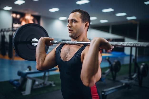 Sterke powerlifter deadlift een barbell in sportschool doen