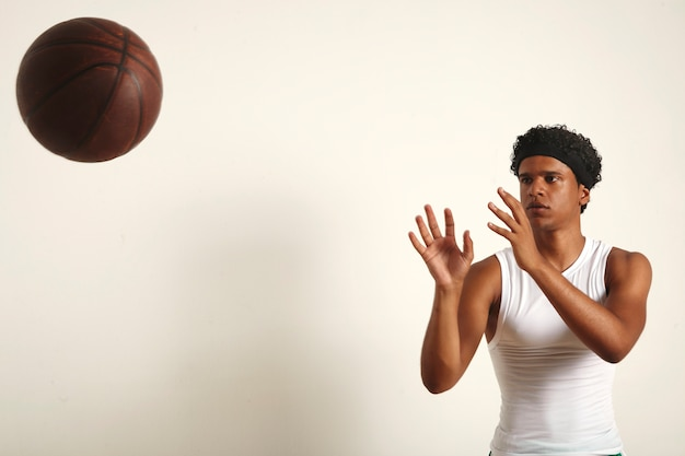 Sterke serieuze zwarte atleet met een afro in een effen wit mouwloos shirt die een donkerbruine vintage basketbal op wit gooit