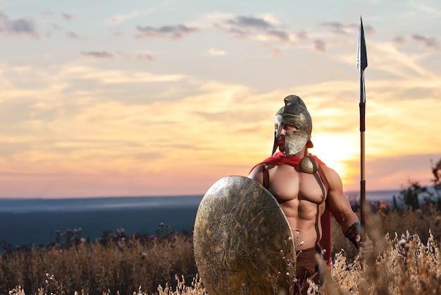 Sterke spartaanse krijger in gevechtskleding met een schild en een speer