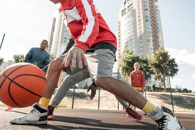 Sterke spieren. close-up van sterke mannelijke benen tijdens het basketbalspel