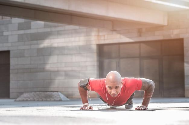 Sterke spieren. sterke jonge man liggend op de vloer tijdens het doen van push-ups tijdens de training
