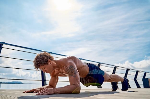 Sterke sportieve man met ontbloot bovenlijf, gekleed in korte broek en sneakers, doet plankoefeningen tijdens het sporten...