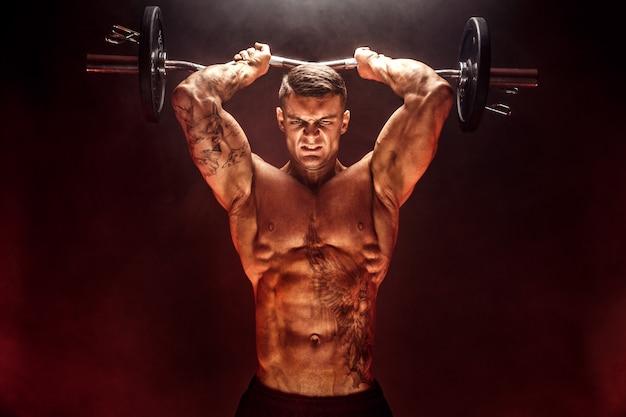 Sterke sportman die zware domoor in rook opheft