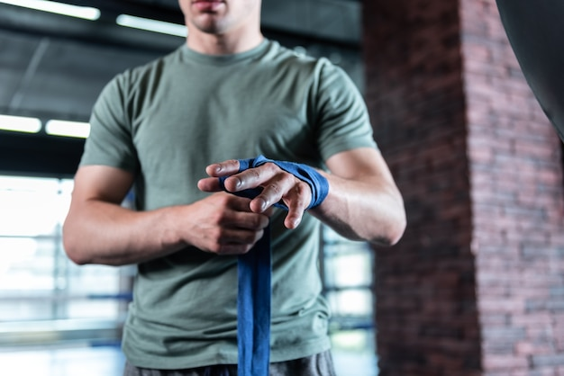 Sterke sportman. sterke spier sportman draagt kaki shirt met professionele blauwe pols wraps