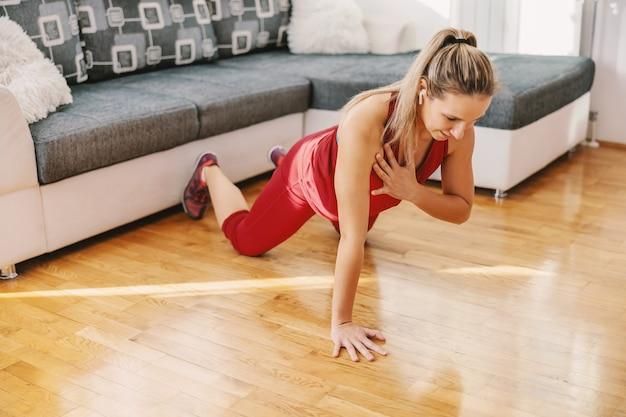 Sterke sportvrouw doet push-ups op de vloer thuis.