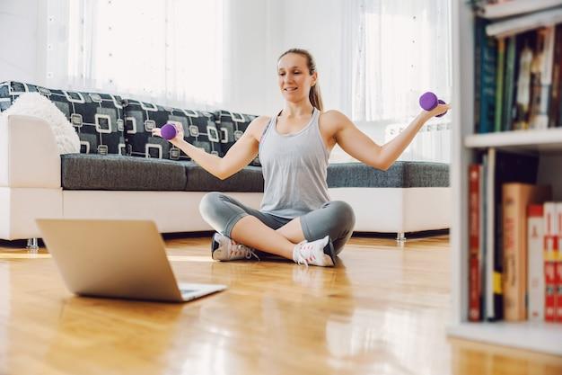Sterke sportvrouw zittend op de vloer thuis en halters op te heffen. ze volgt online tutorials.