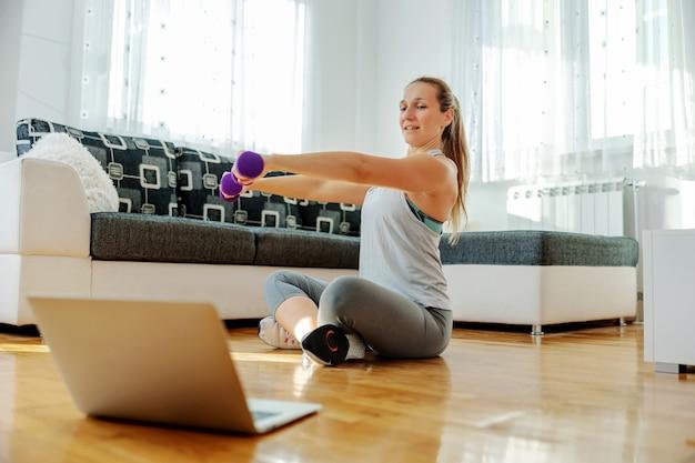 Sterke sportvrouw zittend op de vloer thuis en halters opheffen.