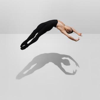 Sterke stijlvolle jonge mannelijke atleet op witte studio achtergrond met schaduwen in jump