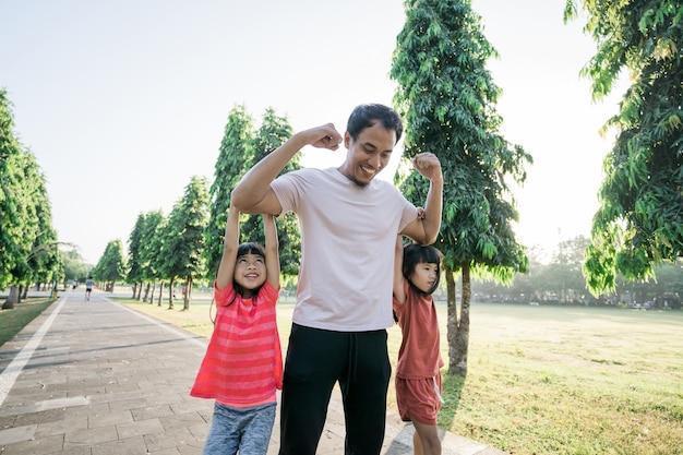 Sterke vader met kinderen die aan zijn arm hangen tijdens het sporten