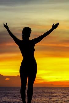 Sterke vertrouwen vrouw open armen onder de zonsopgang aan zee